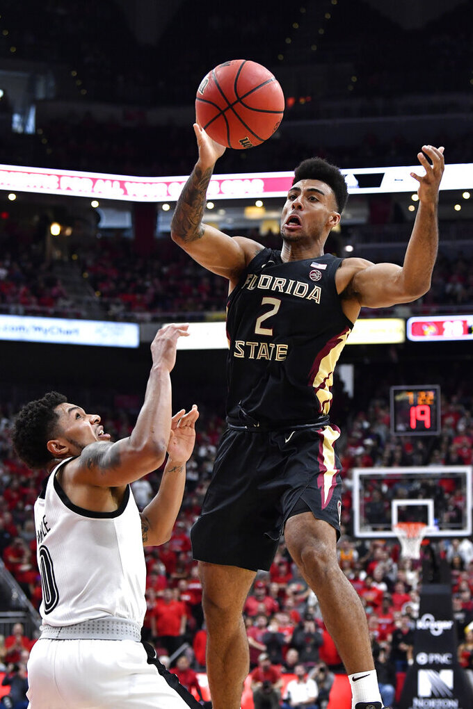 Florida State guard Anthony Polite (2) passes over the defense of Louisville guard Lamarr Kimble (0) during the first half of an NCAA college basketball game in Louisville, Ky., Saturday, Jan. 4, 2020. (AP Photo/Timothy D. Easley)
