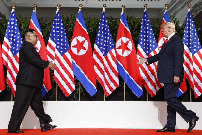 FILE - In this June 12, 2018, file photo, U. S. President Donald Trump, right, and North Korea leader Kim Jong Un walk toward each other at the Capella resort on Sentosa Island in Singapore. North Korea says planned U.S.-South Korean military drills would amount to