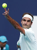 Roger Federer, of Switzerland, tosses the ball on a serve to Radu Albot, of Moldova, during the Miami Open tennis tournament Saturday, March 23, 2019, in Miami Gardens, Fla. (AP Photo/Lynne Sladky)