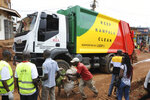 In this photo of Wednesday, July 10, 2019, workers of of Kampala Capital City Authority look on as the truck gets ready to remove garbage under a campaign to encourage people to keep their neighbourhood clean, in Makindye Lukuli area of Kampala, Uganda.  Africa faces a population boom unmatched anywhere in the world, with millions of people moving to fast-growing cities but the decades-old sanitation facilities are crumbling under the pressure.  (AP Photo/Ronald Kabuubi)