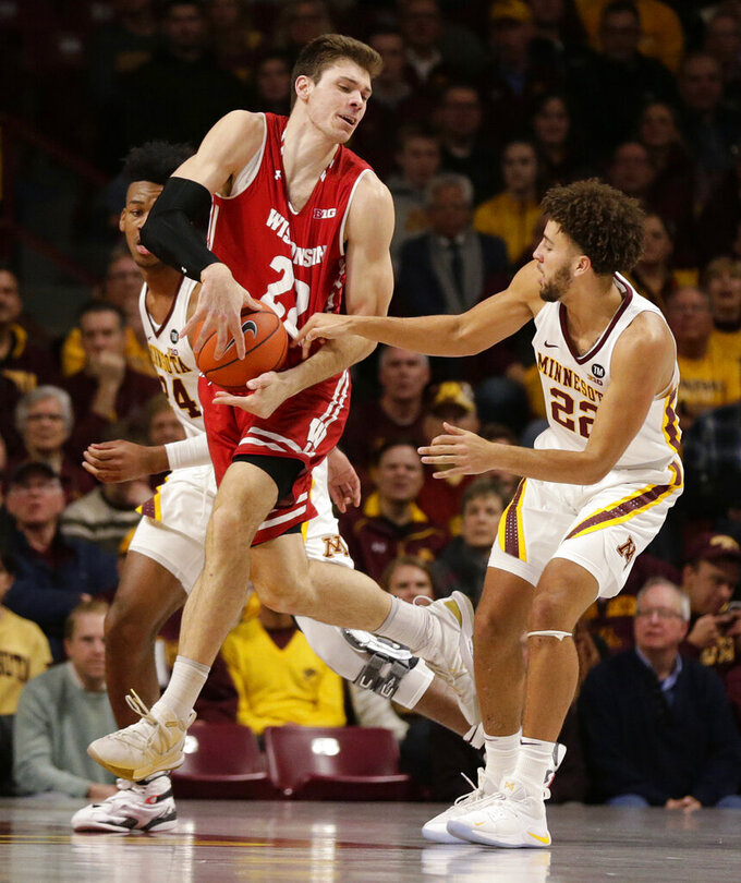 Wisconsin forward Ethan Happ (22) has the ball slapped away by Minnesota guard Gabe Kalscheur (22) during the first half of an NCAA college basketball game Wednesday, Feb. 6, 2019, in Minneapolis. (AP Photo/Andy Clayton-King)