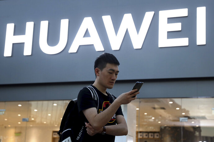 FILE - In this May 20, 2019, file photo, a man uses his smartphone outside a Huawei store in Beijing. Chinese tech giant Huawei is selling a folding smartphone without Google apps or U.S.-made processor chips following sanctions imposed by Washington. The Mate X went on sale Friday, Nov. 15, 2019 on Huawei's online store in China priced at 16,999 yuan ($2,422) and competes with Samsung's Galaxy Fold launched in September. (AP Photo/Ng Han Guan, File)