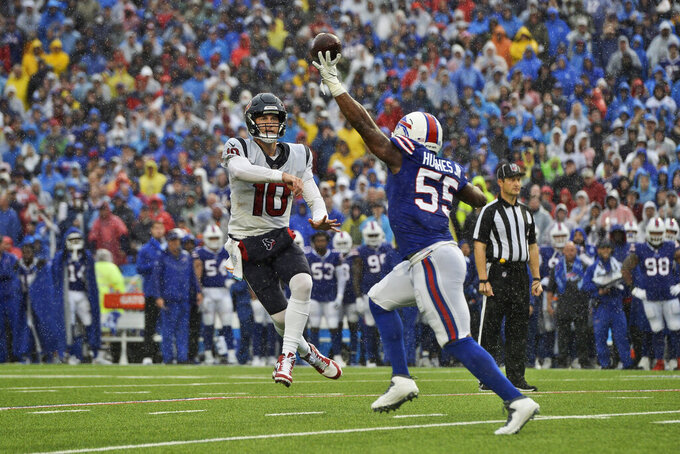 Houston Texans quarterback Davis Mills (10) throws over Buffalo Bills defensive end Jerry Hughes (55) during the first half of an NFL football game, Sunday, Oct. 3, 2021, in Orchard Park, N.Y. (AP Photo/Adrian Kraus)