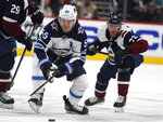 Winnipeg Jets center Mark Scheifele, front, reaches out to control the puck as Colorado Avalanche right wing Joonas Donskoi defends during the second period of an NHL hockey game Tuesday, Dec. 31, 2019, in Denver. (AP Photo/David Zalubowski)