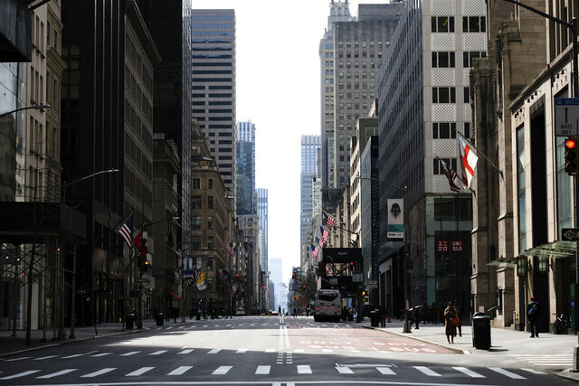 A sparsely occupied Fifth Avenue, usually bustling with traffic, appears at midday on Wednesday, March 18, 2020 in New York. (Photo by Evan Agostini/Invision/AP)