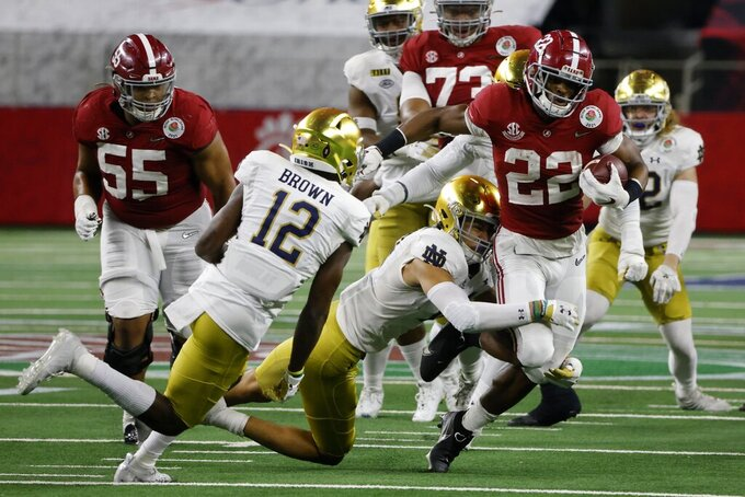 Notre Dame safety DJ Brown (12) and others attempt to stop Alabama running back Najee Harris (22) in the second half of the Rose Bowl NCAA college football game in Arlington, Texas, Friday, Jan. 1, 2021. (AP Photo/Michael Ainsworth)