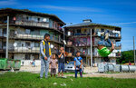 """Children play outside houses of the Roma settlement at the Lunik IX quarter of Slovakia's second largest city of Kosice, Sunday, Sept. 5, 2021. Pope Francis will make his visit to the impoverished Roma community in Slovakia one of the highlights of his pilgrimage to """"the heart of Europe."""" Francis will be the first pontiff to meet the most socially excluded minority group in that Central European country. (AP Photo/Peter Lazar)"""