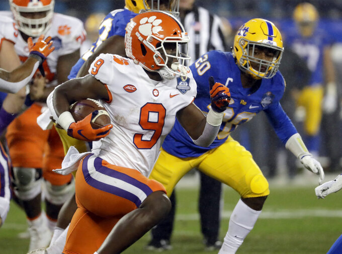 FILE - In this Dec. 1, 2018, file photo, Clemson's Travis Etienne (9) runs past Pittsburgh's Dennis Briggs (20) during the first half of the Atlantic Coast Conference championship NCAA college football game in Charlotte, N.C. Clemson has its own dangerous running game led by Etienne, who has rushed for 1,573 yards at an average of 8.3 yards per clip. Etienne has scored 23 touchdowns, providing a capable complement to the passing game led by freshman Trevor Lawrence. Etienne preserved the Tigers perfect season when he ran for 203 yards and three touchdowns, including the game-winning 2-yard run in a 27-23 come-from-behind victory over Syracuse in September. (AP Photo/Chuck Burton, File)