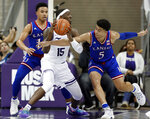 Kansas guard Devon Dotson, left, and guard Quentin Grimes, right,  attempt to strip the ball away from TCU forward JD Miller, center, in the first half of an NCAA college basketball game in Fort Worth, Texas, Monday, Feb. 11, 2019. (AP Photo/Tony Gutierrez)