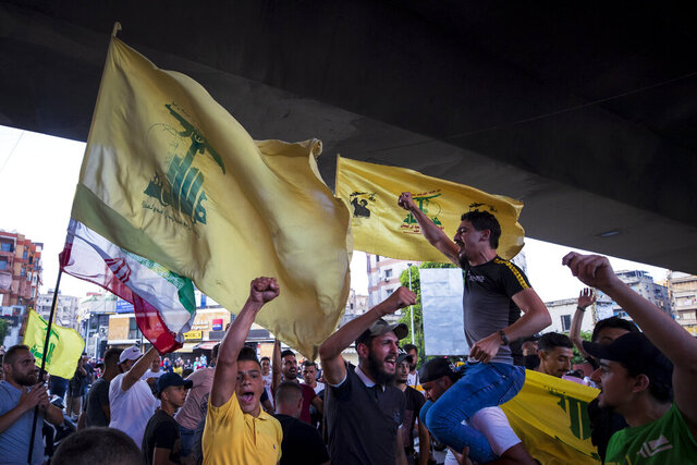 FILE - In this June 28, 2020 file photo, Hezbollah and Amal supporters wave Hezbollah and Iranian flags as they shout slogans against Israel and U.S. during a protest in the southern suburb of Beirut, Lebanon. For many, the Iran-backed Hezbollah now stands at the top of Lebanon's sectarian-based system of power — and so is complicit in the corruption many blame for the port disaster and for driving the country into near bankruptcy. (AP Photo/Hassan Ammar, File)