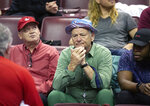 Actor Bill Murray, center, talks to one of the Louisville staff while his son, Luke Murray, coaches in the second half of an NCAA college basketball game against Florida State in Tallahassee, Fla., Monday, Feb. 24, 2020. (AP Photo/Mark Wallheiser)
