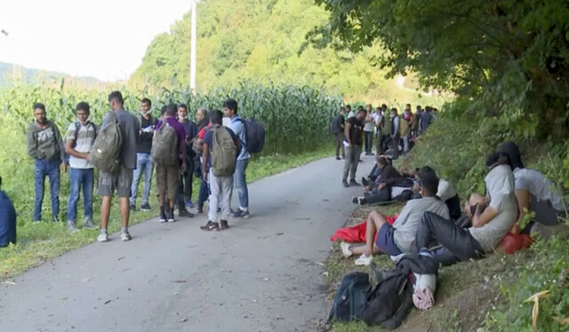 In this grab taken from video migrants who were directed off a railroad by police blocking the path gather, in Bosanska Otoka, Bosnia, Monday, Aug. 24, 2020. Bosnia's quarreling ethnic leaders have put migrants amassed in the country while seeking entry to Europe at the center of a a political tug-of-war. Local authorities in the northwestern Krajina region have set up roadblocks to prevent migrants from entering the area under their jurisdiction, leaving hundreds trapped on the side of a road without access to food or shelter. (AP)