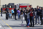 Shoppers hug after being escorted from the Tanforan Mall in San Bruno, Calif., Tuesday, July 2, 2019. Police are searching for suspects after at least two people were wounded in a mall shooting near San Francisco on Tuesday that led to region-wide transit delays at rush hour. (AP Photo/Stephanie Mullen)