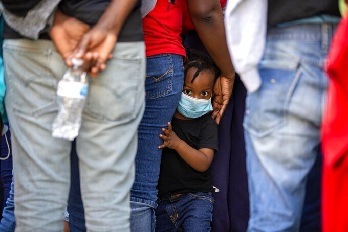 FILE - In this April 23, 2020 file photo, a child looks at the camera as Haitians who were deported from the U.S. line up as they arrive at a hotel where they will be quarantined as a measure against the spread of the new coronavirus in Tabarre, Haiti. (AP Photo/Dieu Nalio Chery, File)