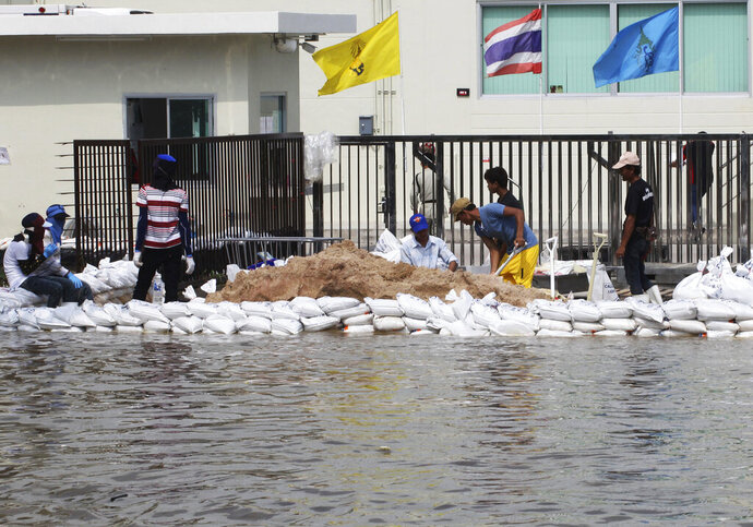 FILE - In this Oct. 9, 2013, file photo, workers build a water barrier with sandbags as floodwater threaten their factory at Amata Nakorn industrial estate in Chonburi province, eastern Thailand. The number of people threatened by climate change-triggered flooding is about three times higher than previously thought, a new study says. But it's not because of more water. It's because the land, especially in Asia and the developing world, is several feet lower than what space-based radar has calculated, according to a study in the journal Nature Communications Tuesday, Oct. 29, 2019. (AP Photo/Apichart Weerawong, File)