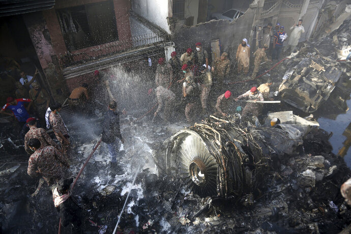 Volunteers look for survivors of a plane that crashed in residential area of Karachi, Pakistan, May 22, 2020. An aviation official says a passenger plane belonging to state-run Pakistan International Airlines carrying more than 100 passengers and crew has crashed near the southern port city of Karachi. (AP Photo/Fareed Khan)