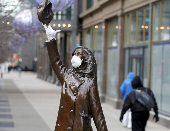The Mary Tyler Moore statue on Nicollet Mall got a mask and rubber glove, perhaps for levity in the face of the Coronavirus, and seen Wednesday, April 1, 2020, in downtown Minneapolis. (David Joles/Star Tribune via AP)