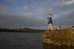 Jago Haag, 9, plays at the water's edge at sunset, in Auckland Saturday, Sept. 4, 2021. The southern winter that just ended in New Zealand was the warmest ever recorded, and scientists say that climate change is driving temperatures ever higher. (Sylvie Whinray/New Zealand Herald via AP)