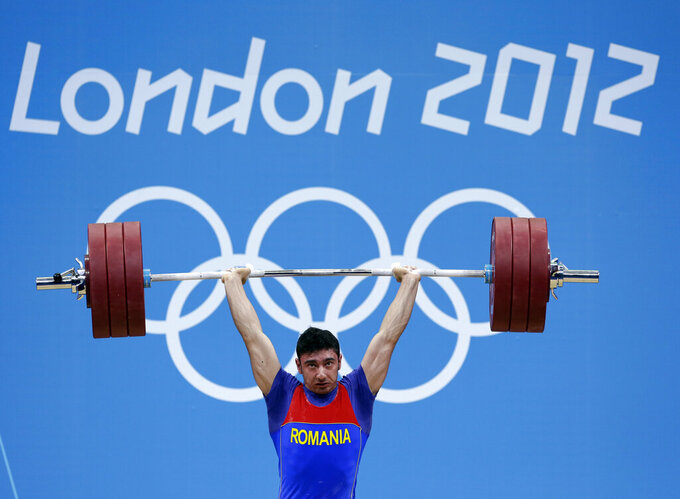 FILE - In this Tuesday, July 31, 2012 file photo, Razvan Constantin Martin of Romania competes during the men's 69-kg, group A, weightlifting competition at the 2012 Summer Olympics, in London. Two Romanian weightlifters have been stripped of their 2012 London Olympics medals for positive tests for steroids. It brings London's record total of doping cases at any Summer or Winter Games to 77. The International Olympic Committee says silver medalist Roxana Cocos and bronze medalist Razvan Martin tested positive for multiple steroids in reanalysis of their samples. (AP Photo/Hassan Ammar)