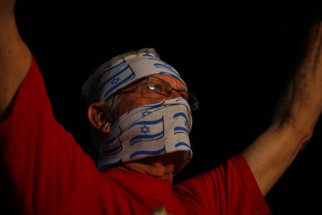 An Israeli protester covers his face with representations of the national flag in Tel Aviv, Israel, Tuesday, Oct. 6, 2020, during a nationwide lockdown to curb the spread of the coronavirus. (AP Photo/Ariel Schalit)