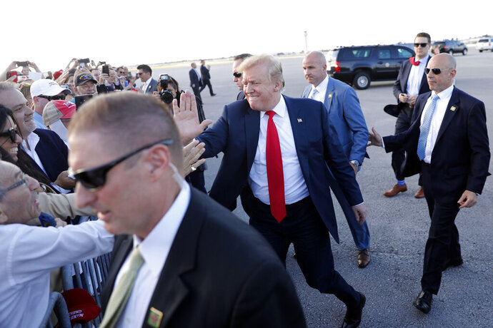 President Donald Trump greets people at Palm Beach International Airport, Thursday, April 18, 2019, in West Palm Beach, Fla. Trump is spending the Easter weekend as his Mar-a-Lago estate. (AP Photo/Pablo Martinez Monsivais)