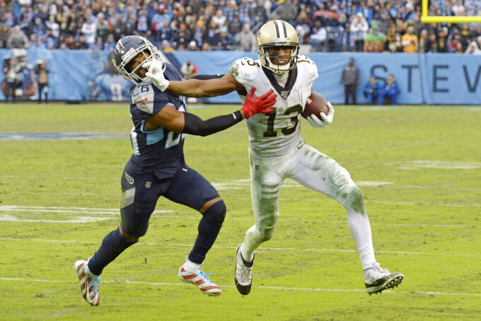 File-This Dec. 22, 2019, file photo shows New Orleans Saints wide receiver Michael Thomas (13) pushing past Tennessee Titans cornerback Logan Ryan (26) after Thomas makes a reception in the second half of an NFL football game in Nashville, Tenn. The catch gave Thomas the single-season pass reception record. Regardless of the record stream of receptions by Thomas, the sacks by Chandler Jones and lengthy field goals by nearly every placekicker, the headlines regularly were about referees and field judges. (AP Photo/Mark Zaleski,File)