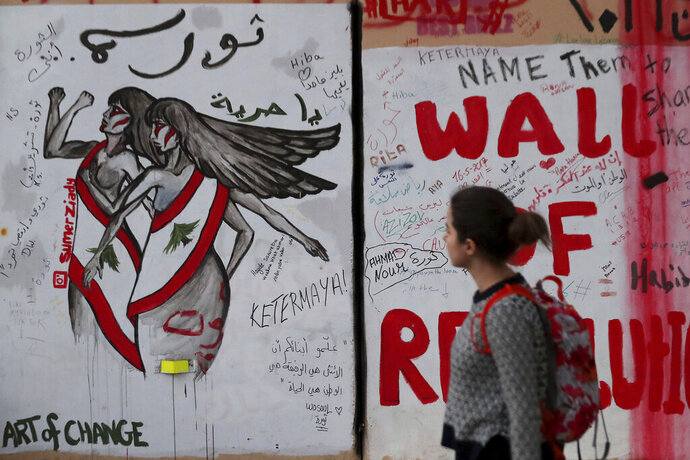 In this Tuesday, Nov. 26, 2019 photo, a woman looks at a wall at United Nations Headquarters, decorated with graffiti in Arabic that reads,