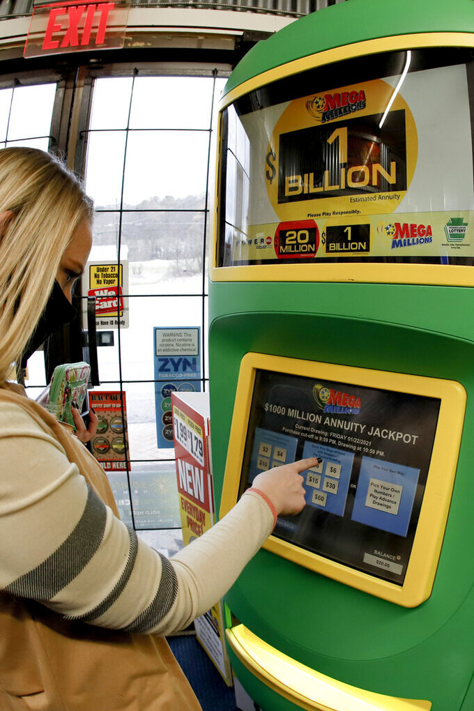 A patron, who did not want to give her name, uses the lottery ticket vending kiosk at a Smoker Friendly store to purchase tickets for the Mega Millions lottery drawing, Friday, Jan. 22, 2021, in Cranberry Township, Pa. The jackpot for the Mega Millions lottery game has grown to $1 billion ahead of Friday night's drawing after more than four months without a winner. (AP Photo/Keith Srakocic)