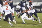 Penn State quarterback Sean Clifford (14) scrambles for a first down as Illinois defensive back Derrick Smith (2) gives chase during the first quarter of an NCAA college football game in State College, Pa., on Saturday, Dec. 19, 2020. (AP Photo/Barry Reeger)