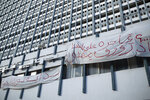 Banners are hung on a building in Tunis' landmark Avenue Habib Bourgiba, where massive protests took place in 2011, on the tenth anniversary of the uprising , in Tunis, Thursday, Jan. 14, 2021. Banners read