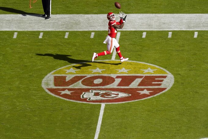 Voting signage is seen on the field as Kansas City Chiefs running back Le'Veon Bell catches a pass during warmups before an NFL football game against the New York Jets on Sunday, Nov. 1, 2020, in Kansas City, Mo. (AP Photo/Charlie Riedel)
