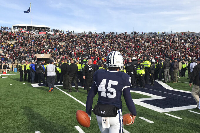 Yale punter Jack Bosman watches as demonstrators stage a protest on the field at the Yale Bowl disrupting the start of the second half of an NCAA college football game between Harvard and Yale, Saturday, Nov. 23, 2019, in in New Haven, Conn. (AP Photo/Jimmy Golen)