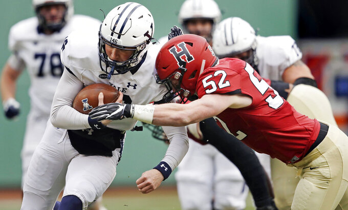 Yale quarterback Griffin O'Connor, left, tries to elude Harvard linebacker Cameron Kline (52) while scrambling for a gain during the first half of an NCAA college football game at Fenway Park in Boston, Saturday, Nov. 17, 2018. (AP Photo/Charles Krupa)