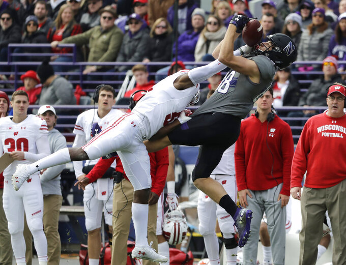 Northwestern wide receiver Bennett Skowronek, right, catches the ball against Wisconsin cornerback Rachad Wildgoose during the first half of an NCAA college football game in Evanston, Ill., Saturday, Oct. 27, 2018. (AP Photo/Nam Y. Huh)