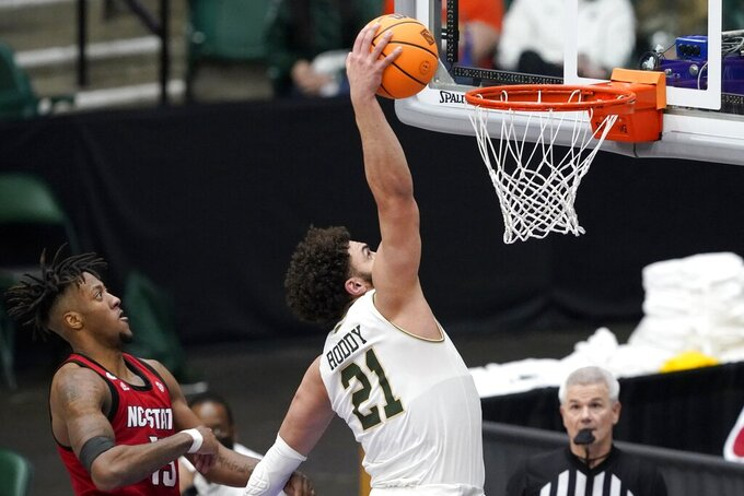 Colorado State guard David Roddy (21) dunks after getting past North Carolina State forward Manny Bates (15) during the second half of an NCAA college basketball game in the quarterfinals of the NIT, Thursday, March 25, 2021, in Frisco, Texas. (AP Photo/Tony Gutierrez)