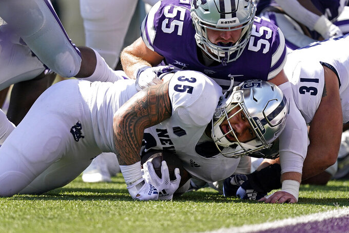 Nevada running back Toa Taua (35) is tackled by Kansas State linebacker Cody Fletcher (55) during the first half of an NCAA college football game Saturday, Sept. 18, 2021, in Manhattan, Kan. (AP Photo/Charlie Riedel)