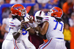 Florida quarterback Emory Jones, left, throws a pass as he get a block from offensive lineman Ethan White (77) during the first half of the team's NCAA college football game against Florida Atlantic, Saturday, Sept. 4, 2021, in Gainesville, Fla. (AP Photo/John Raoux)