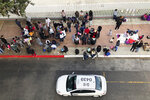 FILE - In this Nov. 10, 2019, file photo, migrants gather at the U.S.-Mexico border in Tijuana, Mexico, to hear names called from a waiting list to claim asylum in the U.S. U.S. authorities wield extraordinary power available in public health emergencies, like the coronavirus pandemic, to expel Mexicans and many Central Americans immediately to Mexico and waive immigration laws that include rights to seek asylum. (AP Photo/Elliot Spagat, File)