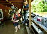 FILE - In this June 2, 2019, file photo, Emily Kientzel empties the water out of her grandmother Joan FitzGerald's boot that filled with floodwater from the Mississippi River, as they check on the home of a friend outside of Portage des Sioux, Mo. The pair are standing on the second story balcony of the home that has more than a foot of water in it. The prolonged flooding along the Mississippi River will cost more than $2 billion in repairs and cleanup, the Mississippi River Cities and Towns Initiative, and advocacy group for river communities, said Tuesday, June 25, 2019.  (David Carson/St. Louis Post-Dispatch via AP, File)