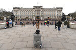 Tourists take photographs outside Buckingham Palace, in London, Friday, Jan. 10, 2020. In a statement Prince Harry and his wife, Meghan, said they are planning