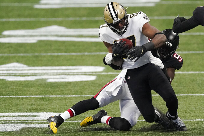 New Orleans Saints running back Tony Jones (37) stopped by Atlanta Falcons linebacker Foye Oluokun (54) during the first half of an NFL football game, Sunday, Dec. 6, 2020, in Atlanta. (AP Photo/John Bazemore)
