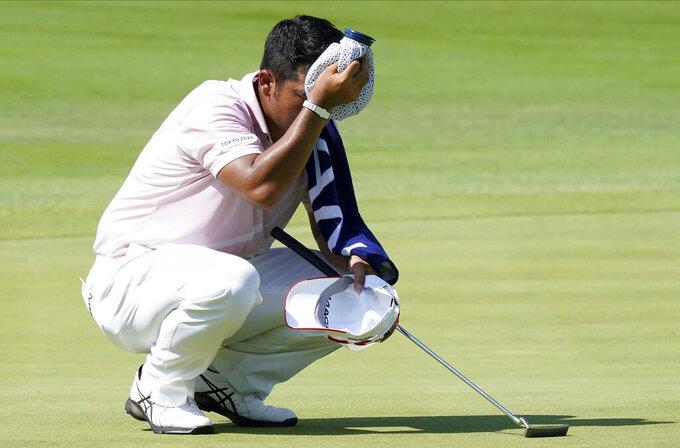 Hideki Matsuyama of Japan dries hi sweat on the 12th green during the third round of the men's golf event at the 2020 Summer Olympics Saturday, July 31, 2021, in Kawagoe, Japan. (AP Photo/Matt York)