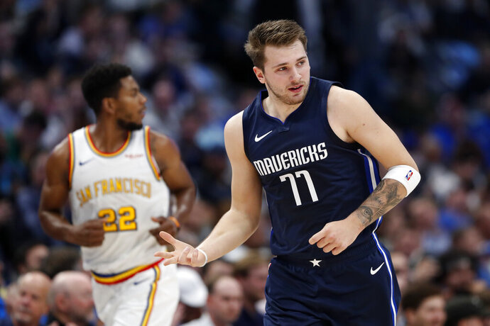 Dallas Mavericks forward Luka Doncic (77) celebrates sinking a 3-point basket as Golden State Warriors forward Glenn Robinson III (22) follows behind in the first half of an NBA basketball game in Dallas, Wednesday, Nov. 20, 2019. (AP Photo/Tony Gutierrez)
