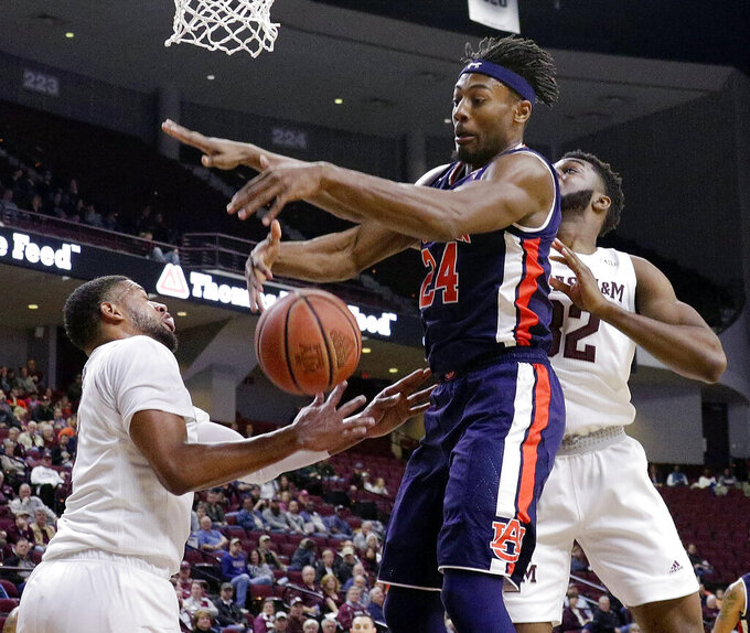 Auburn forward Anfernee McLemore (24) battles for a rebound between Texas A&M guard Savion Flagg, left, and forward Josh Nebo (32) during the first half of an NCAA college basketball game, Wednesday, Jan. 16, 2019, in College Station, Texas. (AP Photo/Michael Wyke)