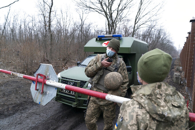A Ukrainian serviceman speaks on a on the walkie-talkie as military medics arrive at a military base to vaccinate troops near the front-line town of Krasnohorivka, eastern Ukraine, Friday, March 5, 2021. The country designated 14,000 doses of its first vaccine shipment for the military, especially those fighting Russia-backed separatists in the east. But only 1,030 troops have been vaccinated thus far. In the front-line town of Krasnohorivka, soldiers widely refuse to vaccinate. (AP Photo/Evgeniy Maloletka)