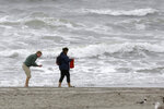 The Atlantic Ocean churns as people collect items along the shoreline Tuesday, Aug. 4, 2020, in Atlantic City, NJ. Tropical Storm Isaias spawned tornadoes and dumped rain during an inland march up the U.S. East Coast, including New Jersey, on Tuesday after making landfall as a hurricane along the North Carolina coast. (AP Photo/Jacqueline Larma)