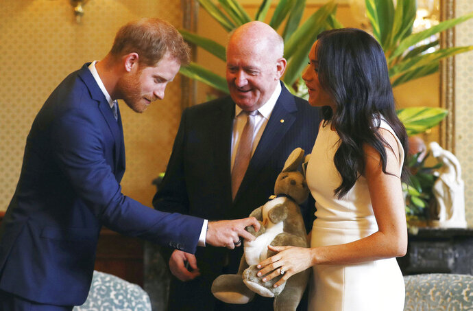 Britain's Prince Harry, right, reacts as Meghan, right, Duchess of Sussex holds a toy kangaroo given by Australia's Governor General Sir Peter Cosgrove, centre, in Sydney, Australia, Tuesday, Oct. 16, 2018. Prince Harry and his wife Meghan are on a 16-day tour of Australia and the South Pacific.(Phil Noble/Pool via AP)