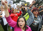 Protesters hold signs and shout slogans during a rally against a visit by President Donald Trump, Tuesday, March 13, 2018, in Beverly Hills, Calif. (AP Photo/Ringo H.W. Chiu)