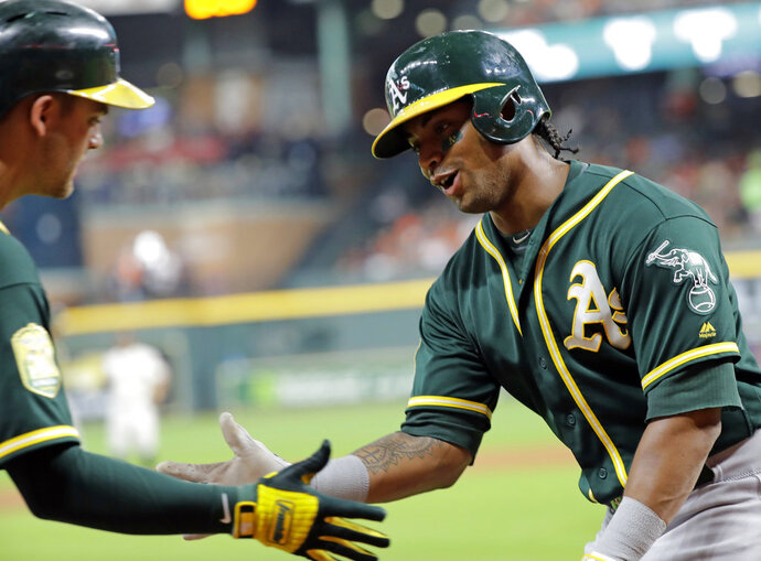 Oakland Athletics' Khris Davis, right, is congratulated by Chad Pinder after scoring during the first inning of a baseball game against the Houston Astros on Wednesday, July 11, 2018, in Houston. (AP Photo/David J. Phillip)