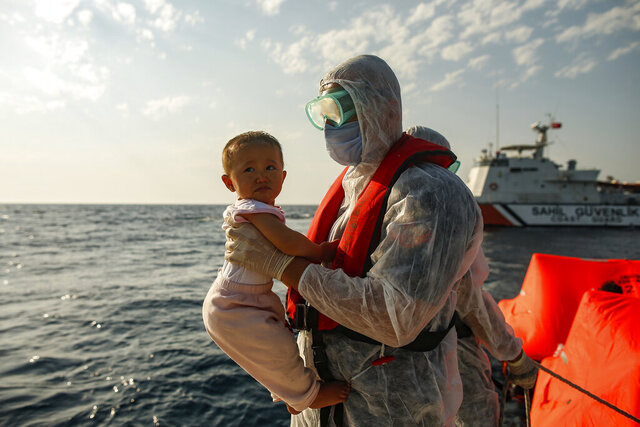 A Turkish coast guard officer, wearing protective gear to help prevent the spread of coronavirus, carries a child off a life raft during a rescue operation in the Aegean Sea, between Turkey and Greece, Saturday, Sept. 12, 2020. Turkey is accusing Greece of large-scale pushbacks at sea — summary deportations without access to asylum procedures, in violation of international law. The Turkish coast guard says it rescued over 300 migrants